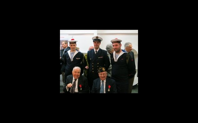 Seated, from left to right: Mr. Robert Aubin and Mr. Harvey Segal, Chevaliers of the Legion of Honor, surrounded by French naval officers.